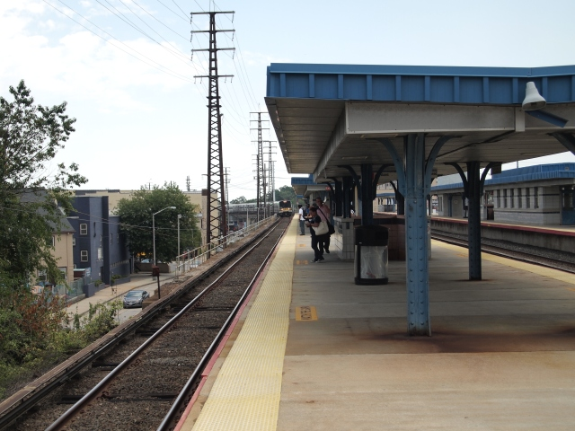 A LIRR train pulls around a slight curve and intro an elevated platform.